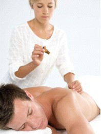 Therapist dropping essential oils on man's back