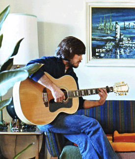 Man playing Guild 12-string guitar